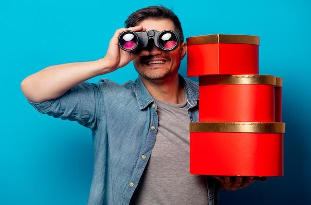 Verraste man met verrekijker en rode geschenken Premium Foto