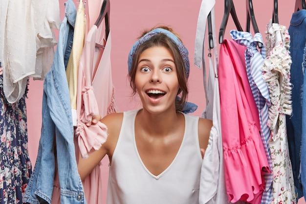 Verraste mooie vrouw die met wijd geopende mond en ogen kijkt terwijl ze in de buurt van een rek met kleren in haar kamer staat, geschokt door zo'n verscheidenheid aan jurken en blouses. lichaamstaal concept Gratis Foto