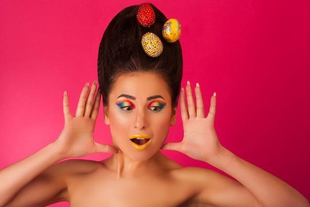Verraste mooie vrouw met eieren op haar haar op roze Premium Foto