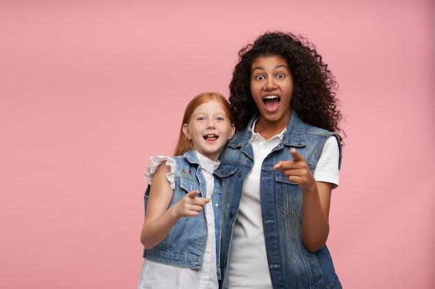 Verraste vrolijke jonge dames in vrijetijdskleding met grote ogen en mond open, vooruit wijzend met opgeheven wijsvinger terwijl ze poseren op roze Gratis Foto