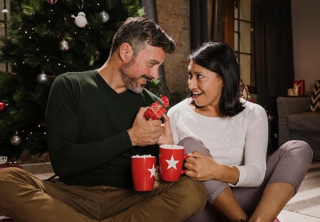 Verraste vrouw die haar echtgenoot met een gift bekijkt Gratis Foto