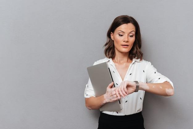 Verraste vrouw in bedrijfskleren met laptop in hand kijkend op polshorloge op grijs Gratis Foto