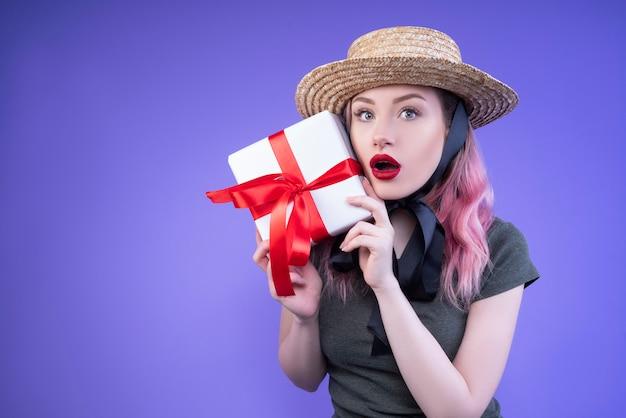 Verraste vrouw in een strohoed die het geschenk in haar handen toont Gratis Foto