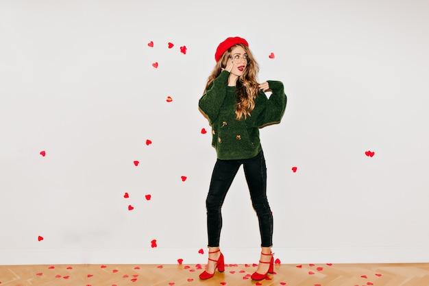 Verraste vrouw in rode sandalen en baret die zich onder hartconfettien bevindt Gratis Foto