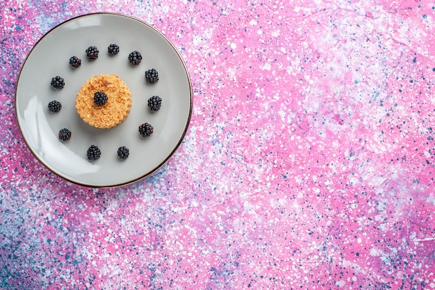 Verre bovenaanzicht van kleine cake met bessen op roze oppervlak Gratis Foto