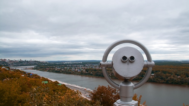 Verrekijker op het observatiedek. uitzicht op de bergen van de stad en het herfstbos. Premium Foto
