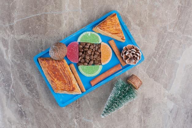 Verrukkelijk arrangement van jam, koffiebonen, kyata's, kaneelstokjes, dennenappels en een boomfiguur op marmer. Gratis Foto