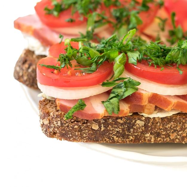 Vers bereide sandwich met ham op een plaat geïsoleerd op een witte achtergrond Premium Foto