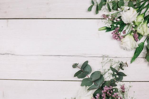 Vers bloemboeket op wit houten bureau Gratis Foto