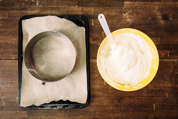 Vers deeg in de kom en pan met perkamentpapier op hout Premium Foto