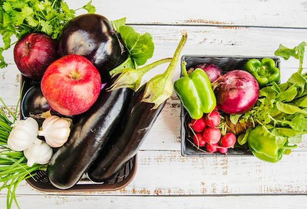 Vers fruit; en groenten in plastic mand over houten tafel Gratis Foto