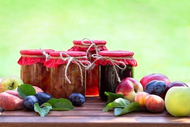 Vers fruit en zelfgemaakte potten jam op houten tafel in wazig natuurlijke tuin. conserven van perziken, nectarines, pruimen, appel Premium Foto