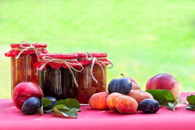 Vers fruit en zelfgemaakte potten jam op wazig natuurlijke tuin Premium Foto