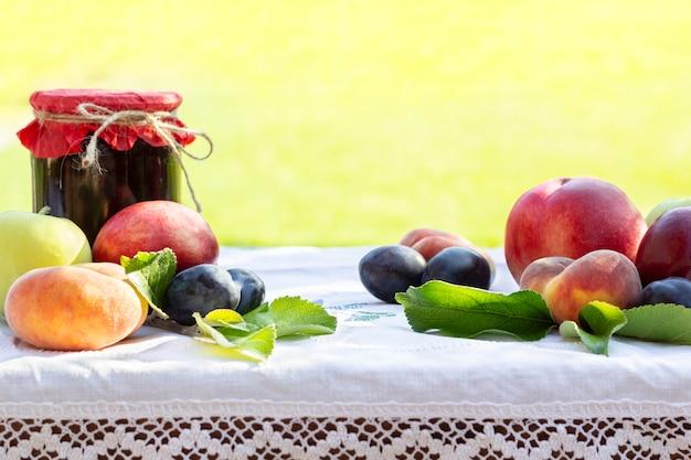 Vers fruit perziken, nectarines, pruimen en zelfgemaakte potten jam Premium Foto