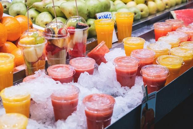 Vers fruitcocktails en plakjes verschillende soorten fruit in een glas op een aanrecht in de markt Premium Foto