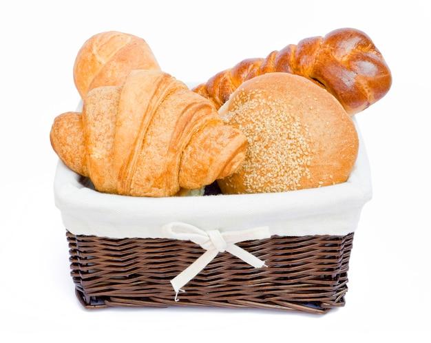 Vers gebakken broodjes in een mand op wit Premium Foto