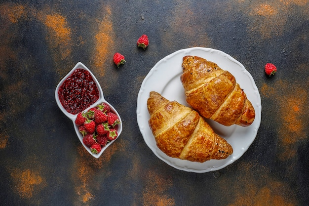 Vers gebakken croissants met frambozenjam en frambozenfruit. Gratis Foto