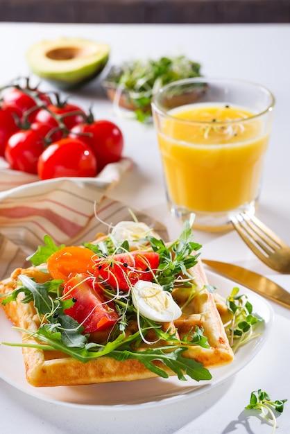 Vers gebakken zoete belgische wafels met eieren, tomaten, micro groen en avocado geserveerd op een bord met jus d'orange op marmer Premium Foto