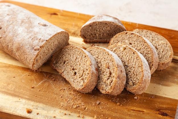 Vers gehakt bruin roggebrood, plakjes op houten snijplank, ontbijtconcept, horizontaal, kopie ruimte, plaats voor tekst Premium Foto