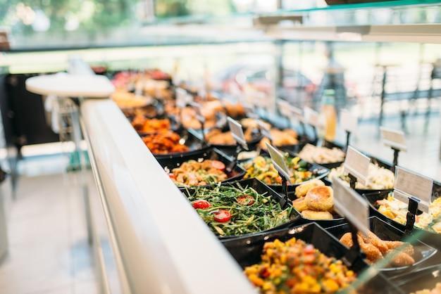 Vers gekookt voedsel in de winkel, niemand. showcase met bereide salades en vleesproducten in de markt Premium Foto