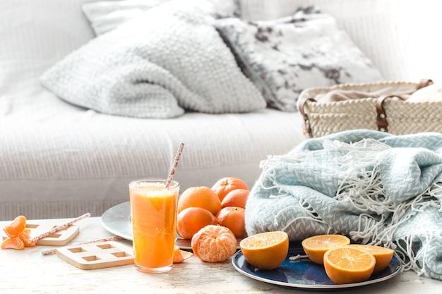 Vers geteelde biologische verse jus d'orange in het huis, met een turquoise deken en een fruitmand Premium Foto