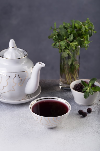 Vers gezette thee wordt in een kom gegoten, daarnaast is een chocoladetaart versierd met een takje verse kruiden Premium Foto