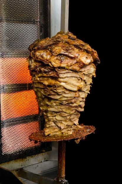 Vers grieks gyros-vlees dat op een stok wordt geroosterd. geïsoleerd op zwarte achtergrond Premium Foto