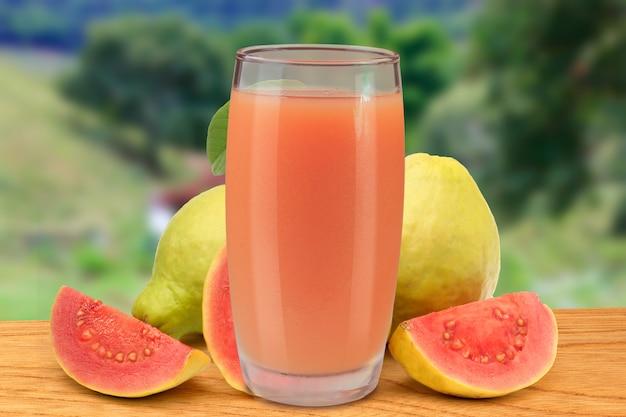 Vers guavesap in glaskop op houten lijst van aard en landbouwbedrijf Premium Foto