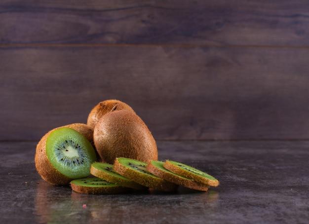 Vers kiwifruit op donkere oppervlakte Gratis Foto