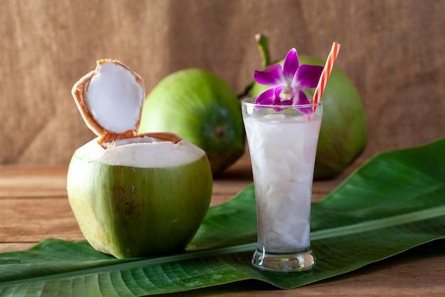 Vers kokosnotenwater in een glas op een houten raad voor het drinken Premium Foto