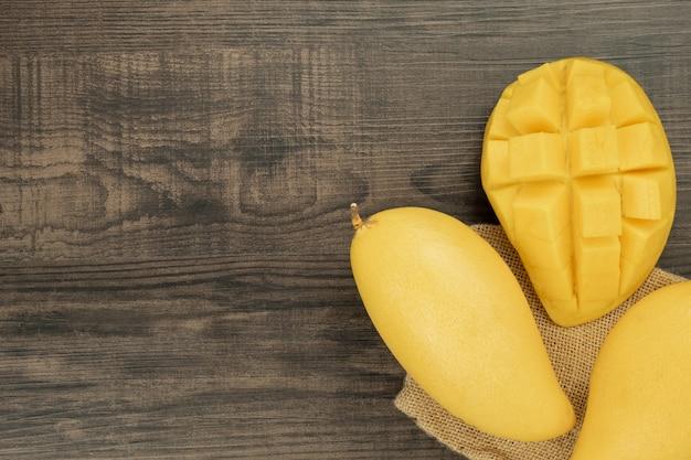Vers mango bovenaanzicht. houten achtergrond en kopie ruimte voor tekst toevoegen. Premium Foto