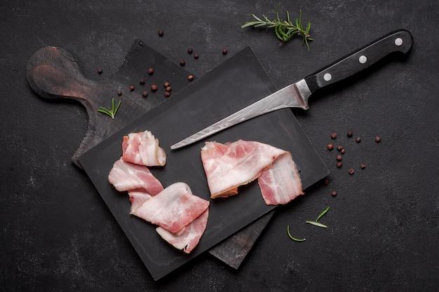 Vers ongekookt bacon op houten raad met mes Gratis Foto