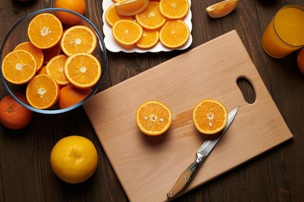 Vers oranje fruit geheel en in plakjes gesneden op een houten tafel, snijden b Premium Foto