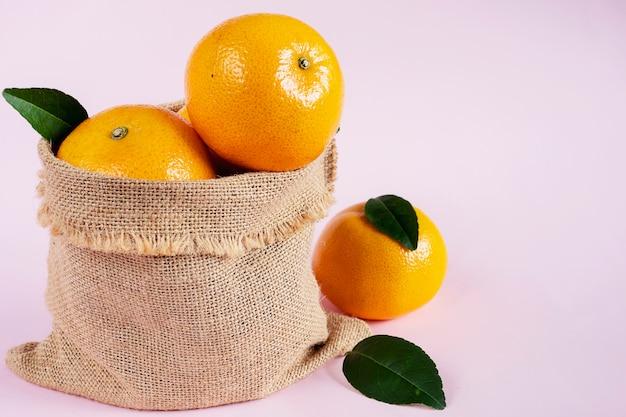 Vers sappig oranje fruit dat over lichtrose wordt geplaatst Gratis Foto