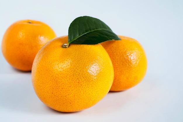 Vers sappig oranje fruit dat over wit wordt geplaatst Gratis Foto