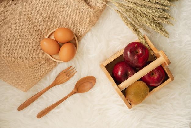 Vers sappig rood appelen en kiwifruit in houten mand met eieren op houten achtbaan en jutedoek Premium Foto
