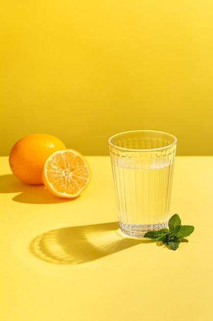 Vers stilstaand water op een gele achtergrond met citroen en munt Premium Foto