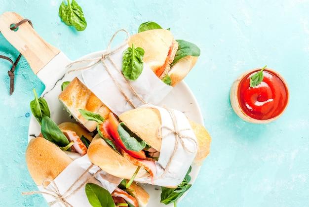 Vers stokbroodsandwich met de tomaten van de baconkaas en spinazie lichtblauwe achtergrond Premium Foto