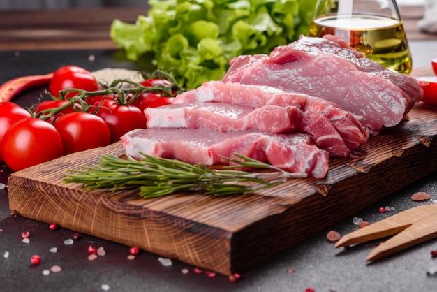 Vers stukjes varkensvlees klaar om in de keuken te koken. sirloin medaillons steaks op een rij klaar om te koken Premium Foto