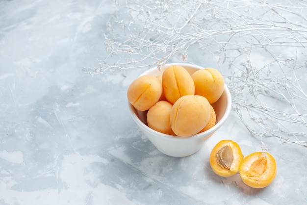 Vers zoet abrikozen zacht fruit binnen plaat op wit bureau, fruit vers zomer voedsel maaltijd vitamine Gratis Foto