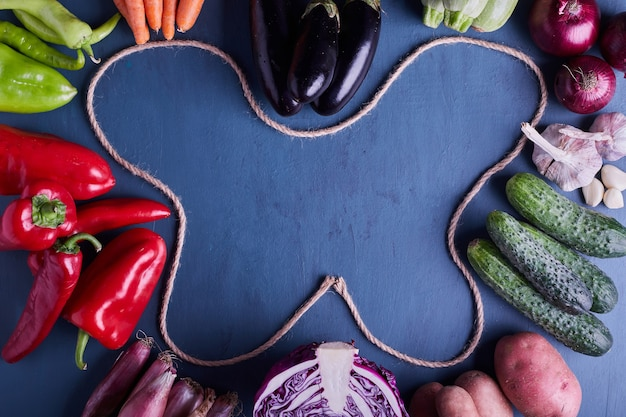 Verscheidenheid aan groenten in het frame van blauwe tafel. Gratis Foto