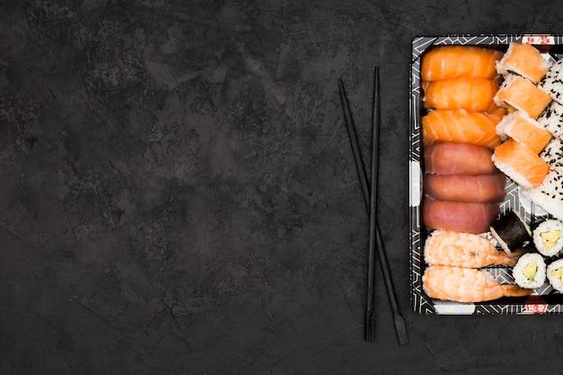 Verscheidenheid van aziatische visbroodjes op dienblad en eetstokjes over geweven achtergrond met ruimte voor tekst Premium Foto