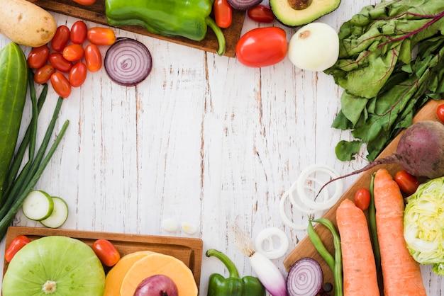 Verscheidenheid van biologische groenten op witte houten bureau Gratis Foto