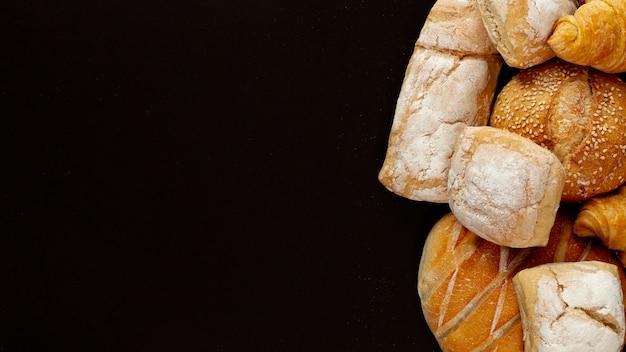 Verscheidenheid van brood op zwarte achtergrond Gratis Foto
