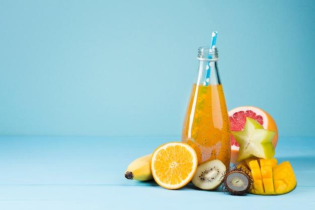 Verscheidenheid van fruit en sap op blauwe achtergrond Gratis Foto