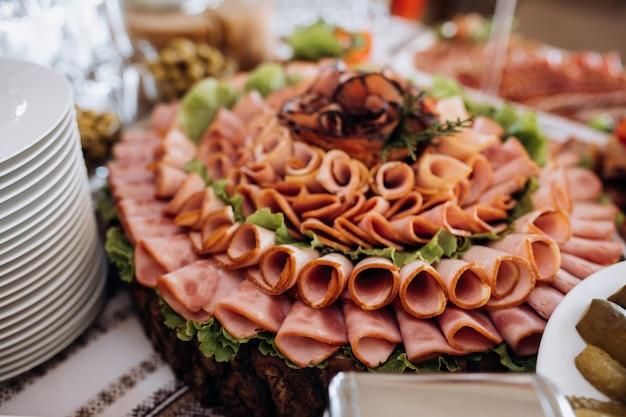 Verscheidenheid van gesneden ham en versierd met salade Gratis Foto
