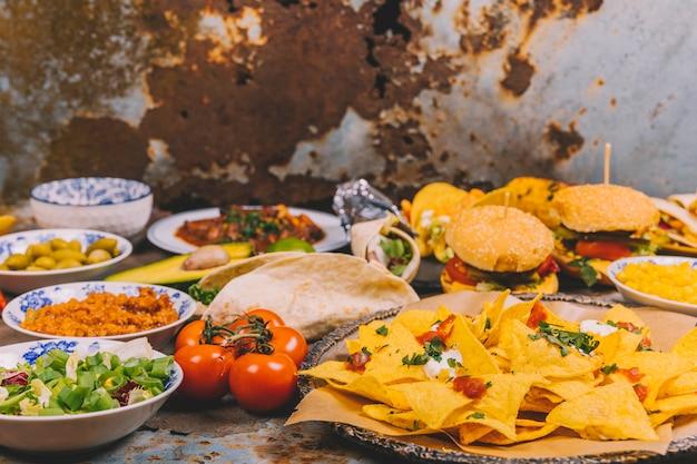 Verscheidenheid van heerlijke mexicaanse gerechten over roestige metalen achtergrond Gratis Foto