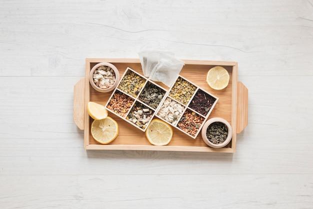 Verscheidenheid van kruiden en gedroogde chinese chrysanthemum bloemen gerangschikt in kleine container op houten lade Gratis Foto