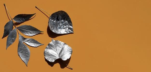 Verscheidenheid van zilver geschilderde bladeren en kopie ruimte Gratis Foto