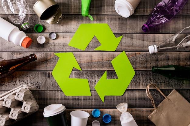 Verschillende afvalmaterialen met recyclingssymbool op lijstachtergrond. Premium Foto